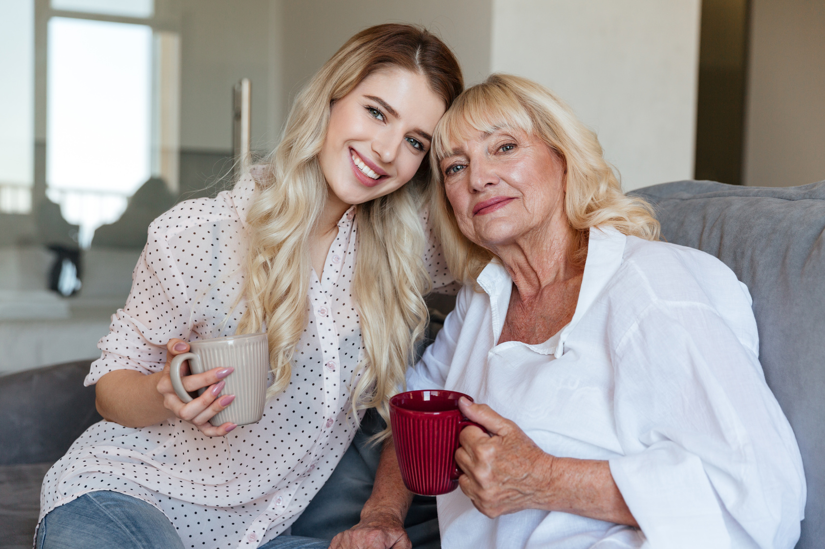 Picture of smiling young lady sitting at home with her grandmother drinking tea. Looking camera.